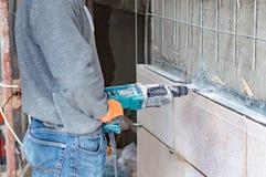 Процесс сверлить отверстия в бетонной стене стоковые изображения