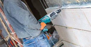 Процесс сверлить отверстия в бетонной стене стоковое изображение