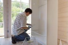 Процесс собирать мебель, мастер собирает белый шкаф используя электрический сверлильный аппарат стоковое изображение rf