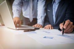 Процесс сыгранности, молодые бизнесмены вручает указывать на документ a стоковое фото