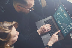 Процесс Coworking в офисе 2 молодых коллеги используя компьютер Женщина нося черный пуловер и сидя на софе Стоковое Изображение
