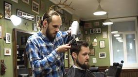 Процесс Hairstyling Конец-вверх волос парикмахера суша молодого бородатого человека видеоматериал