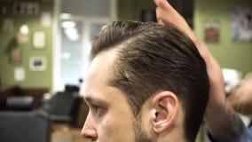 Процесс Hairstyling Конец-вверх волос парикмахера суша молодого бородатого человека сток-видео