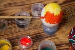 Процесс paiting пасхальное яйцо с оранжевой щеткой, чонсервными банками, древесиной Стоковые Фотографии RF