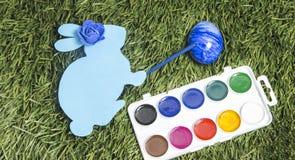 Прочешите зайчик с отметкой на ей рука ` s и роза сини на ей яичко картины головы ` s в синь Стоковые Фото