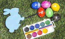 Прочешите зайчик с paintbrush на ем рука ` s, крася eggs в 6 цветов стоковое изображение