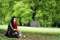 Прочитайте книгу сидя под деревом цветения стоковые фото