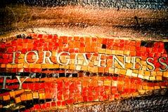 Прощение слова в плитке мозаики стоковые фото