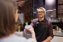 Продавец давая кофейную чашку к клиенту женщины на кафе Стоковые Изображения