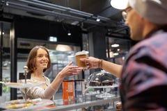 Продавец давая кофейную чашку к клиенту женщины на кафе Стоковое Фото
