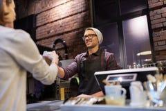 Продавец давая кофейную чашку к клиенту женщины на кафе Стоковое фото RF
