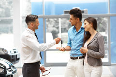 Продавец автомобилей давая ключ от нового автомобиля к молодым предпринимателям Стоковая Фотография