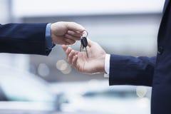 Продавец автомобилей вручая над ключами для нового автомобиля к молодому бизнесмену, конец-вверх Стоковая Фотография