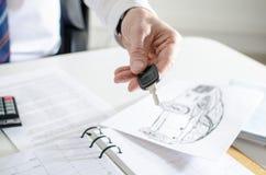 Продавец автомобилей держа ключ Стоковая Фотография RF