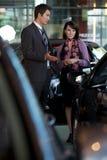 Продавец автомобилей объясняя характеристики автомобиля к клиенту стоковое изображение rf