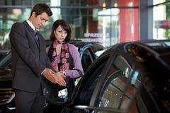 Продавец автомобилей объясняя характеристики автомобиля к клиенту стоковые фото