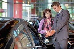 Продавец автомобилей объясняя характеристики автомобиля к клиенту стоковые изображения rf