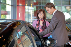 Продавец автомобилей объясняя характеристики автомобиля к клиенту стоковое фото rf