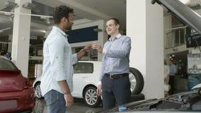 Продавец дает ключи к покупателю в выставочном зале автомобиля сток-видео
