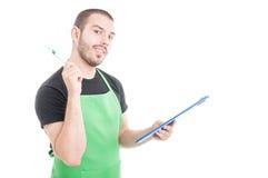 Продавец гипермаркета при отличная идея приходя держащ доску сзажимом для бумаги Стоковые Изображения RF