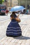 Продавец девушки с конфетой одел в ретро одежде в историческом cit Стоковая Фотография