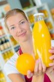 Продавец держа апельсиновый сок апельсина и бутылки Стоковые Изображения