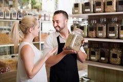 Продавец держа стекло может с высушенными травами Стоковые Фотографии RF