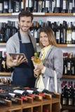 Продавец держа таблетку цифров пока клиент с бутылкой вина Стоковое Изображение RF