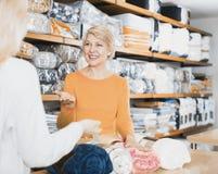 Продавец женщины показывая разнообразные покрывала стоковое изображение