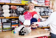 Продавец женщины показывая разнообразные покрывала стоковые фотографии rf