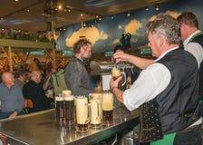 Продавец заполняет кружки пива Пиво проекта на международной зеленой неделе Берлине, 20 01 2016 Стоковая Фотография