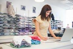 Продавец на магазине одежд стоковое фото