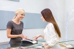 Продавец помогает даме выбрать ювелирные изделия Стоковые Фото