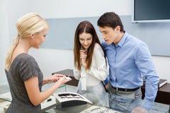 Продавец помогает парам для того чтобы выбрать ювелирные изделия Стоковые Изображения RF
