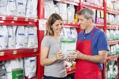 Продавец помогая клиенту в покупая корме для домашних животных на магазине Стоковое фото RF