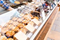 Продавец получает пирог руки дом сделал дисплей scones на квадрате под стеклянной витриной торговая операция улицы в рынке Стоковое Фото