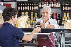 Продавец признавая передвижную оплату от клиента в магазине сыра Стоковое Изображение RF