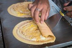 Продавец свертывая закуску улицы плоского блинчика токио Khanom тонко тайскую Стоковая Фотография