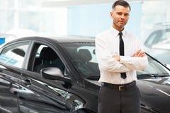 Продавец стоит около совершенно нового автомобиля Выставочный зал автомобиля Стоковая Фотография RF