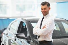 Продавец стоит около совершенно нового автомобиля Выставочный зал автомобиля Стоковые Изображения RF