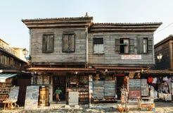 Продавец сувениров сидит в его магазине в старой части Nessebar Ветхий строить для продажи в старом городке стоковая фотография