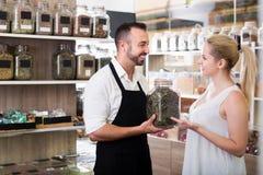 Продавец человека выбирая стекло может с высушенными травами Стоковая Фотография RF