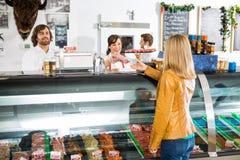 Продавщица давая мясо к женскому клиенту стоковое фото rf