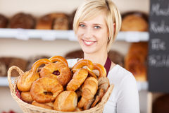 Продавщица в хлебопекарне показывая различные хлебцы хлеба Стоковые Изображения