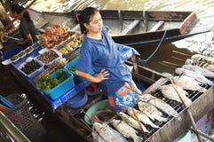 Продавщица жарит ее рыб Стоковые Изображения