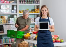 Продавщица показывая таблетку цифров пока старший человек Стоковое Фото