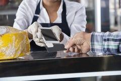 Продавщица признавая оплату от клиента в магазине сыра Стоковые Фотографии RF