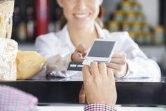 Продавщица признавая оплату от клиента в магазине сыра Стоковые Изображения
