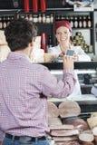 Продавщица признавая оплату от клиента в магазине сыра Стоковое Изображение