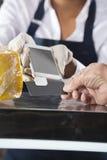 Продавщица признавая оплату от клиента в магазине сыра Стоковые Изображения RF